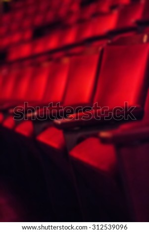Blurred dark background: rows of empty red theater chairs - stock photo