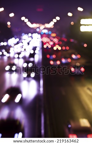 Blurred Defocused Lights of Heavy Traffic on a Wet Rainy City Road at  - stock photo