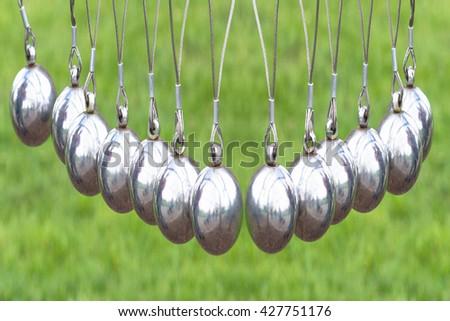 Blurred desirable. Artistic work of my own.  Newton's Cradle or pendulum ball, Newton pendulum also called Newton's cradle.  - stock photo