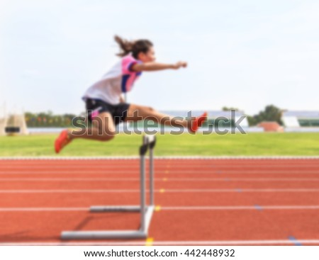 blurred female jump over hurdle during training in stadium - stock photo