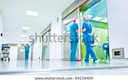 blurred figures wearing medical uniforms in hospital surgery corridor