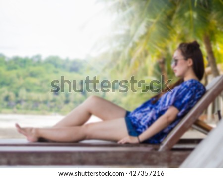 Blurred filter girl sitting on beach bed seeing sea