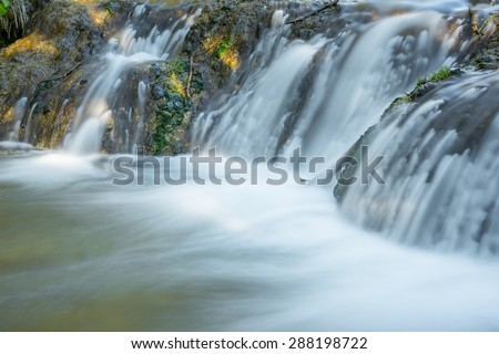 Blurred flowing stream & waterfall at Big Hill Springs Provincial Park in Alberta, Canada - stock photo