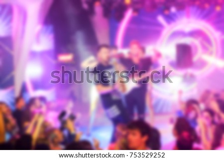 Blurred for background. Night club dj party people enjoy of music dancing sound with colorful light, smoke machine, lights show and dance show. Hands up in earth