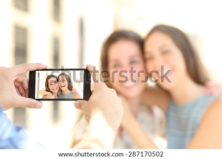 Blurred friends taking photos with a smart phone and showing the photo in the screen on the street - stock photo