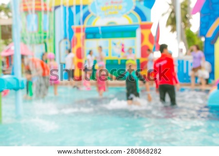 Blurred happy children has fun playing in water fountains in water park with security guard in orange shirt - stock photo