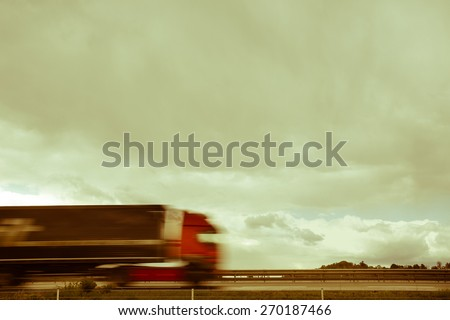 Blurred heavy truck driving fast on a highway, with dramatic sky as a background, in sepia - stock photo