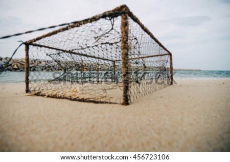 blurred image and closeup rusty crab pot on the sandy beach. focus in the middle - stock photo