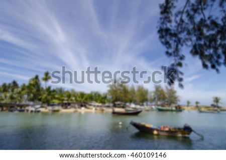 blurred image background,group of traditional fisherman boat moored over village background at sunny day.reflection on the water with cloudy and blue sky.