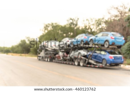 Blurred image big car carrier truck of new cars for batch delivery to dealership. Full load transport truck of new vehicles on country road in San Antonio, TX. Automotive industry abstract background.