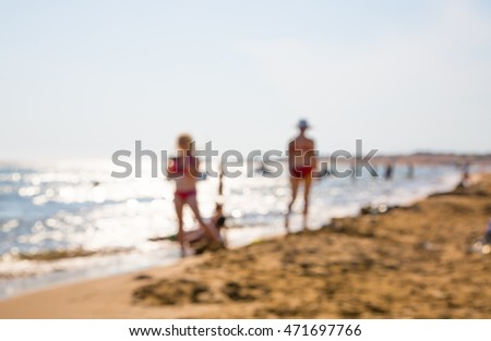 Blurred image for background. People on the beach, walking and playing in the sea against of sun reflection. Greece