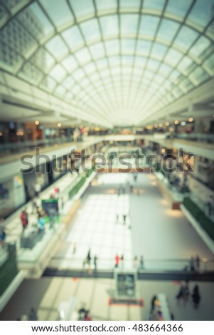 Blurred image interior of main hall shopping mall showing the ice rink and large skylight, natural light from glass roof. Glazed barrel vault spanning central axis, fashion boutique corridor. Vintage.