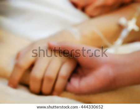 Blurred image of a child holding his mother's hand with iv needle lying on the bed in hospital ward for medicare background