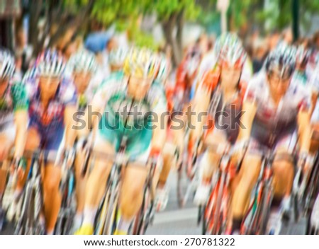 blurred image of a pack of bicycle riders rounding a corner in a race
