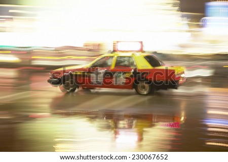 Blurred image of a taxi driving - stock photo
