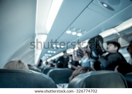 Blurred image of airplane interior in cabin,blue color filter - stock photo