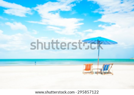 Blurred image of beach chairs and parasol on white sand beach in summer blue sky background