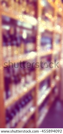 Blurred image of bottles of wine on the shelves in supermarket. - stock photo