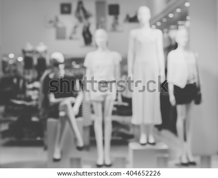 Blurred image of boutique display window with mannequins in fashionable dresses for background. Black and white image. - stock photo