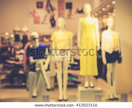 Blurred image of boutique display window with mannequins in fashionable dresses for background. Toned image. Retro effect. - stock photo