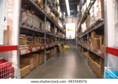 Blurred image of large furniture warehouse with row of aisles and bins from floor to ceiling. Defocused background industrial storehouse interior aisle. Inventory, wholesale, logistic, export concept.