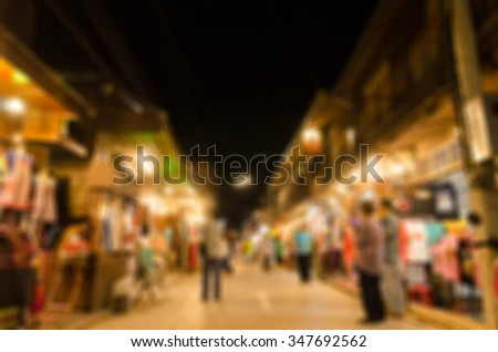Blurred image of people moving in crowded night city street in chiang kan - stock photo