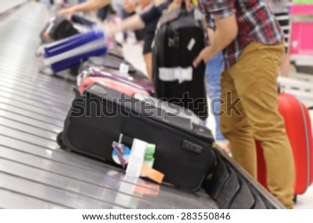 blurred image of people picking up suitcase on luggage conveyor belt in the t airport - stock photo