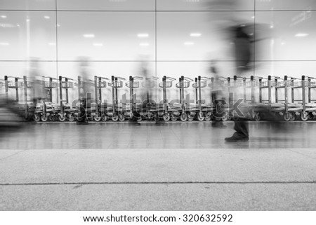 Blurred image of people walking in the airport with a airport trolley as the background. - stock photo