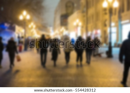 Blurred image of People walking on Arbat street at night, with building in background. Moscow, Russia