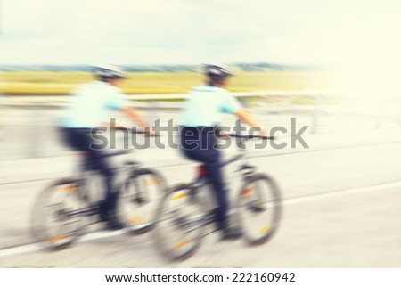 Blurred image of police officers on bicycles in motion.  - stock photo