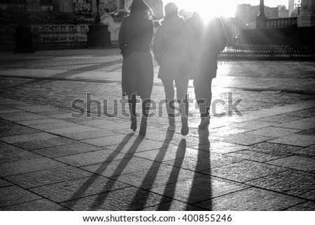 Blurred image of shadows of people leaving in the sunset. BW