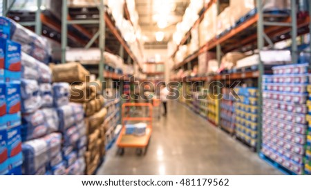 Blurred image of shelves in modern distribution warehouse or storehouse. Defocused background of industrial warehouse interior aisle. inventory, wholesale, logistic and export concept. Panorama.