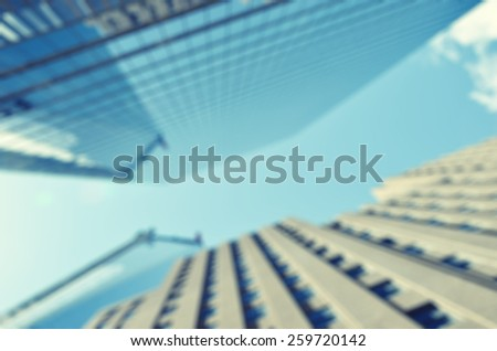 Blurred image of skyscrapers against blue sky - stock photo