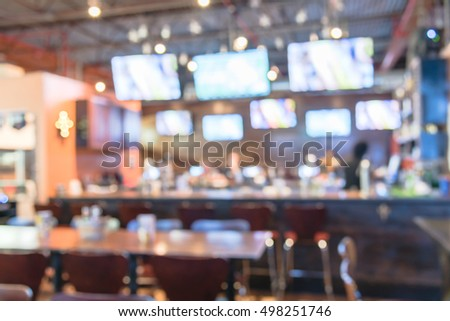 Blurred Image Of Sport And Oyster Bar With TV, Classic Counter, Tables And  Chairs