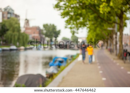 Blurred image of two man walking along green and spacious canal of contemporary city.
