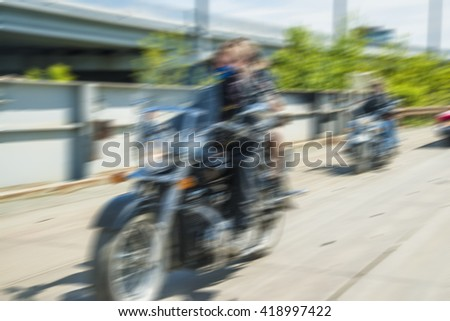 blurred image. Panning shot of Two tourists on chopper motorbike wearing black leather jacket in a sunny day - stock photo