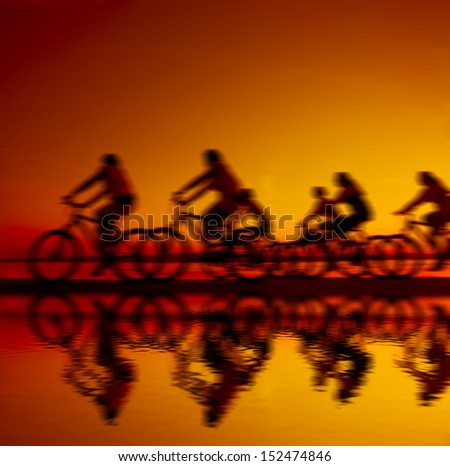 Blurred Image sporty company friends on bicycles outdoors against sunset Blurred Silhouette A lot phases of motion single cyclist along shoreline coast Reflection on water copy Space for inscription - stock photo