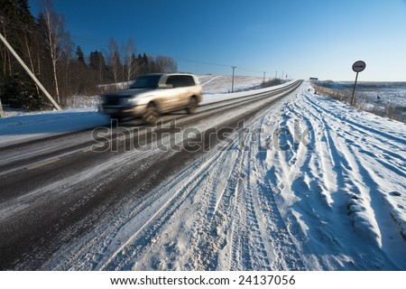 Blurred jeep on rural road in winter - stock photo