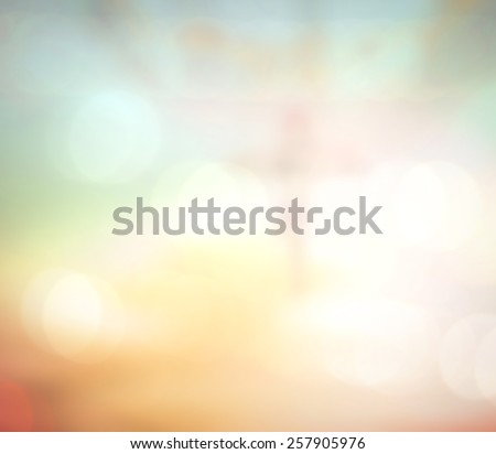 Blurred Jesus on the cross with crown of thorns over beautiful bokeh sunset or sunrise background. - stock photo