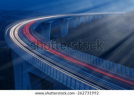 Blurred lights of vehicles driving in night on a tall viaduct,  lit by moonlight, with wind barriers, long exposure - stock photo