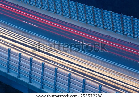 Blurred lights of vehicles driving on a viaduct with wind barriers, long exposure - stock photo