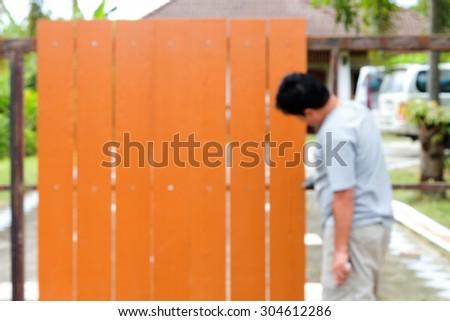 blurred man repairing his gate - stock photo
