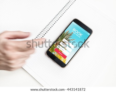 Blurred Man's hand and smartphone with hotel booking online application on screen. Tour reservation, Screen graphics are made up.