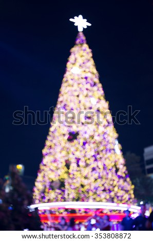 Blurred Merry Christmas tree lighting front the shopping mall at night. Bangkok Thailand.
