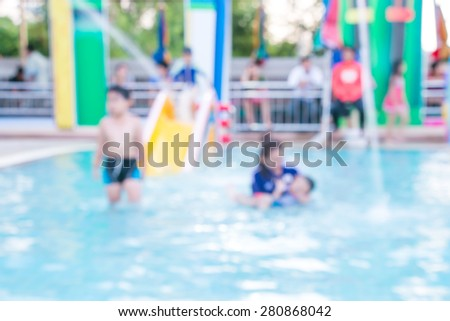 Blurred mom and children has fun playing in water fountains in water park - stock photo