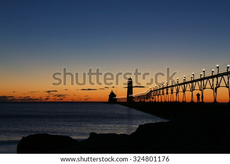 Blurred motion affect with water during sunset at the Grand Haven South Pierhead Lighthouse in Grand Haven State Park in Grand Haven, Michigan - stock photo