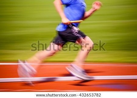 Blurred motion image of a man running in a relay race - stock photo