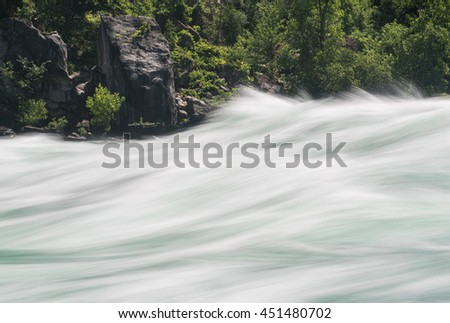 Blurred motion of Class six rapids in river by White Water Walk near whirlpool rapids at Niagara Falls - stock photo