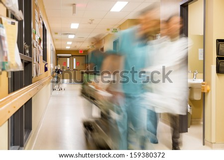 Blurred motion of doctor and nurse pulling stretcher in hospital - stock photo