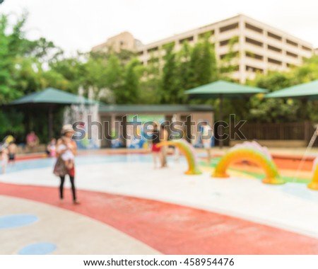 Blurred motion of kids having fun play with water at playground in summer time. Activities for children and family at outdoor aquatic park with water sprinkles and fountain. Amusement park background.